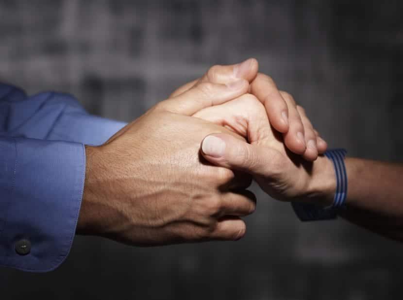 manos que se aprietan con fuerza compasivas