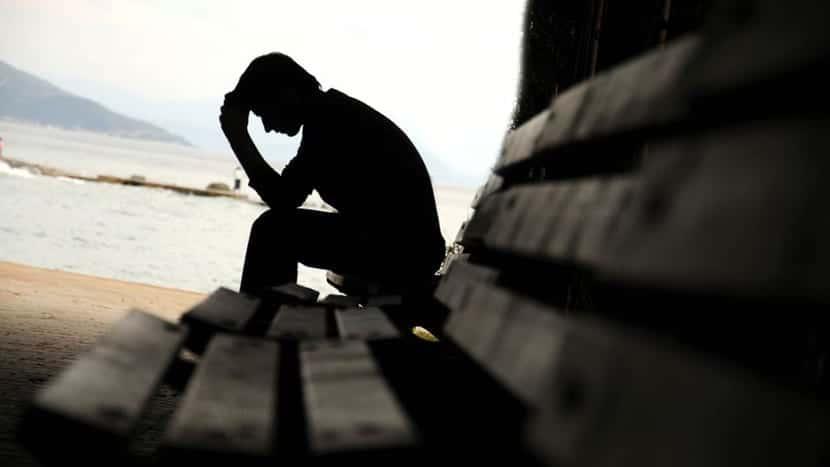 hombre con depresion al lado de la playa