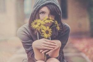 chica enamorada oliendo flores