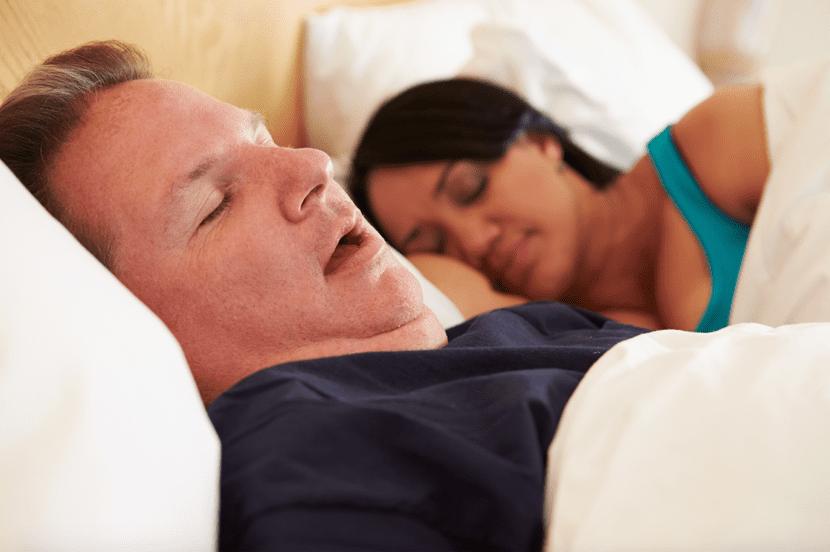 hombre con apnea del sueño durmiendo en pareja